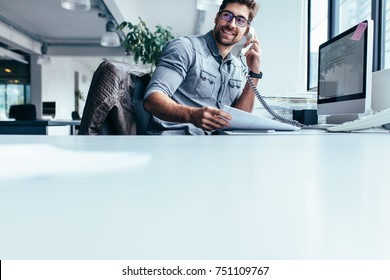 Businessman sitting in office and talking on telephone. Young man using phone at his workplace.