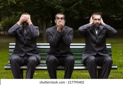 businessman sitting on a bench three times covering his ears,eyes and mouth