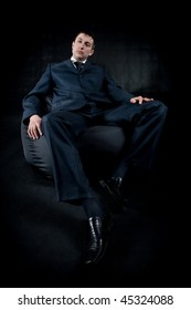 businessman sitting on black chair on dark background