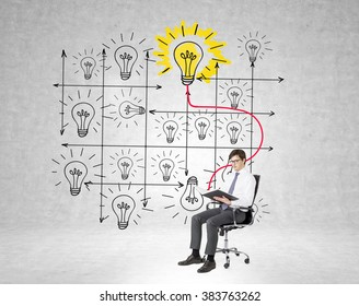 A businessman sitting on a castor chair and reading a book,  system of bulbs drawn behind him, the book and the shining yellow bulb linked. Concrete background. Concept of studying