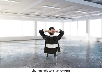 Businessman sitting on the chair in the center of sunny spacious hangar area with concrete floor and windows in floor 3D Render