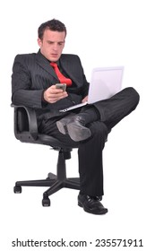 Businessman is sitting on the chair and checking his phone