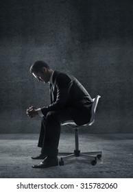 businessman sitting on a chair in dark room