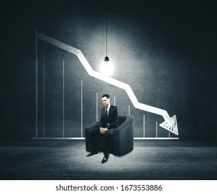 Businessman sitting on chair and drawing falling chart on wall. Leadership and crisis concept