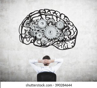 Businessman sitting on chair with hands on head and looking at image of brain with gears on concrete wall. Back view. Concept of mental work.
