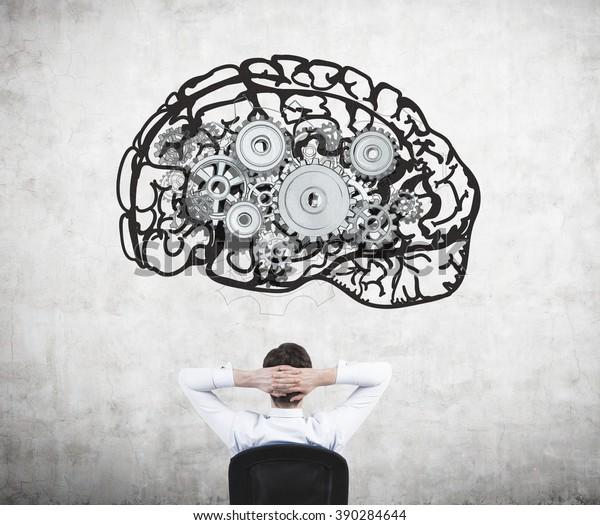 Geschäftsmann sitzend auf Stuhl mit Händen auf Kopf und Blick auf das Bild des Gehirns mit Zahnrädern auf Betonwand. Rückansicht. Konzept der geistigen Arbeit.