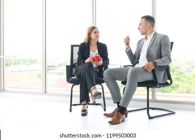 Businessman sitting on chair and talking with his friend or partnership or businesswoman with glass window background