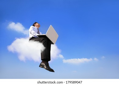 businessman sitting on a cloud working with laptop, low angle view, cloud computing concept