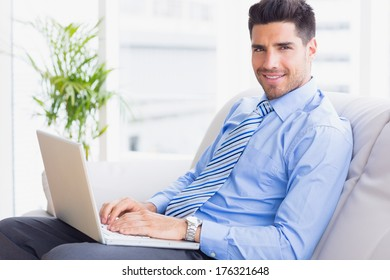 Businessman sitting on couch using his laptop smiling at camera in the office