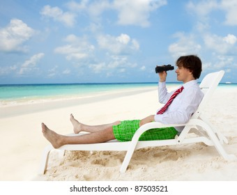 Businessman sitting on the deckchair and looking through binoculars, wearing formal shirt and red tie