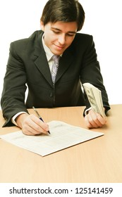Businessman sitting on the desk and holding money in a hand