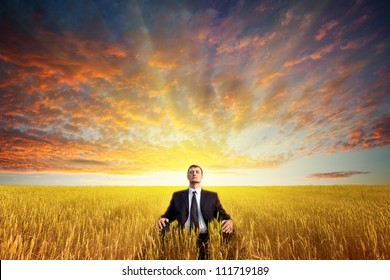 businessman sitting on filed in lotus pose, sunset time