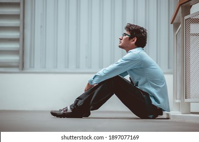 Businessman sitting on the floor after failure and layoff. Man unemployed from company sitting sad outside at overpass background. Men fired from job. Stress manager sit alone.