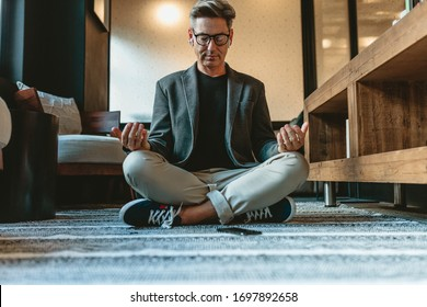 Businessman sitting on floor and meditating in yoga pose. Mature businessman doing relaxation yoga in office lounge.