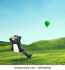 Businessman sitting on green field and looking at air balloon