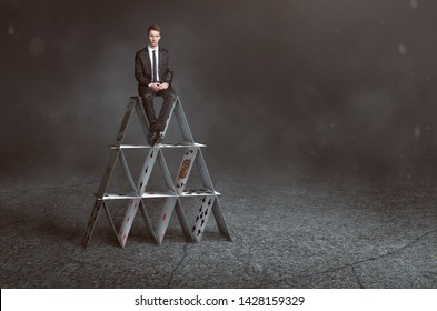 Businessman is sitting on house of cards