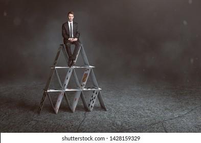 El hombre de negocios está sentado en la casa de las cartas