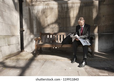 Businessman sitting on outdoor bench reading newspaper
