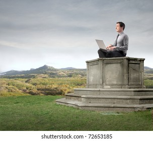 Businessman sitting on a pedestal and using a laptop