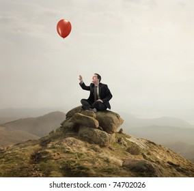 Businessman sitting on a rock and holding a balloon