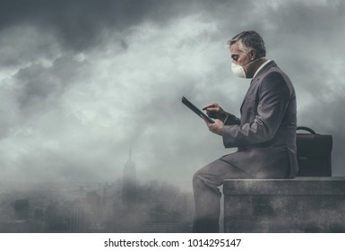 Businessman sitting on a rooftop in a polluted city and using a tablet: environmental pollution and business concept