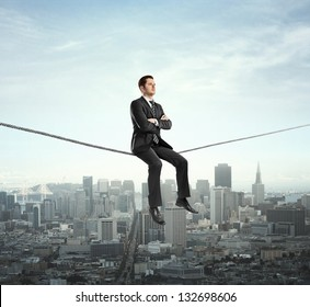 businessman sitting on rope and city