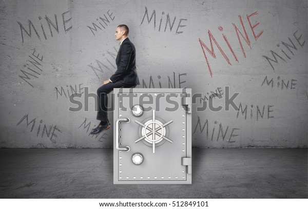 Businessman sitting on the safe on a background of the wall with inscription 'Mine'. Greed and possessiveness. Reliability and protection. Bank vault. Savings account.
