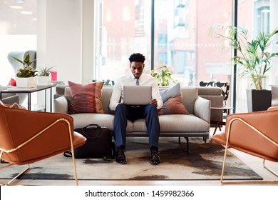 Businessman Sitting On Sofa Working On Laptop At Desk In Shared Workspace Office