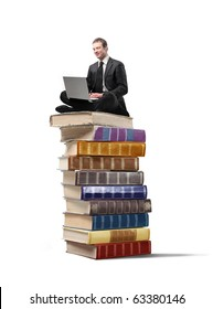 Businessman sitting on a stack of books and using a laptop