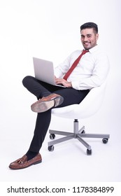 Businessman sitting on white chair isolated. Handsome young indian businessman using laptop portrait, confident smile looks. Full length side shot.