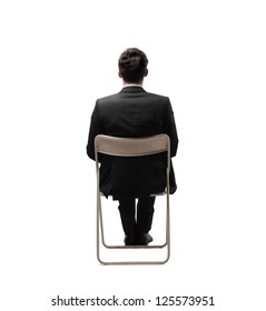 Businessman sitting on a white chair in a completely white location