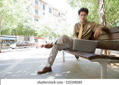 Businessman sitting on a wooden bench in the city using his laptop. Low perspective view.