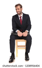 businessman sitting on wooden chair and holding briefcase under his elbows laughs and looks to side, on white background