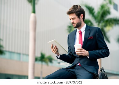 Businessman sitting outdoors and reading information on the digital tablet
