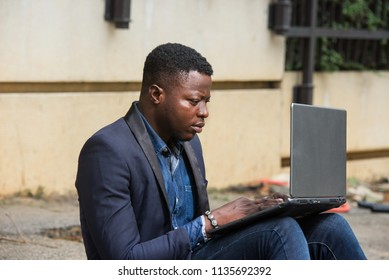 Businessman sitting outside modern office block and working on laptop.