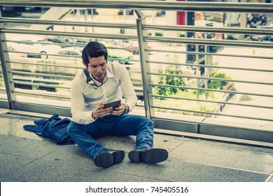 Businessman sitting outside on the ground after being dismissed.