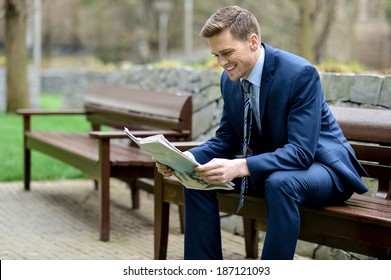 Businessman sitting in park bench, reading a newspaper