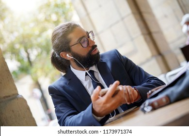 Businessman sitting at restaurant table using smartphone