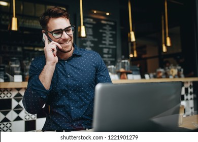 Businessman sitting in a restaurant talking on mobile phone while working on a laptop. Smiling businessman working on laptop sitting in a cafe.