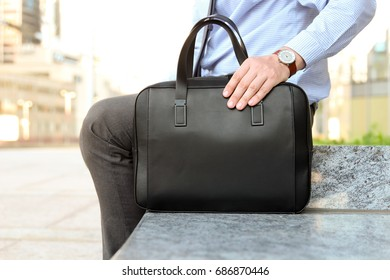 Businessman sitting / resting after working day and holding  a  leather briefcase in his hand