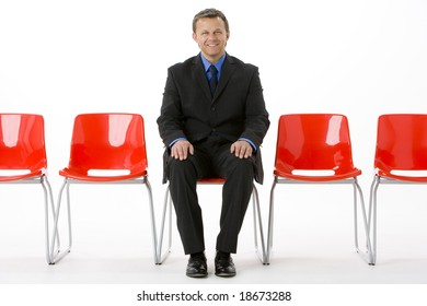 Businessman Sitting In Row Of Empty Chairs