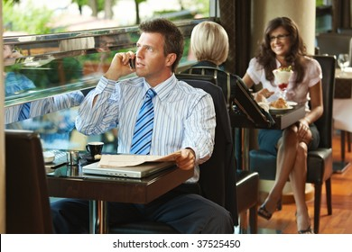 Businessman sitting at table in cafe, reading newspaper and talking on mobile phone.