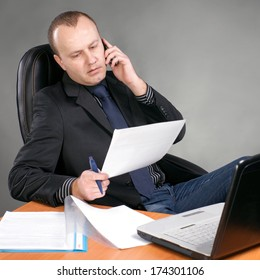Businessman sitting at table with laptop, talking on mobile phone  on a gray background