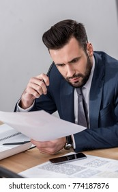 businessman sitting at table and looking at documents with surprise
