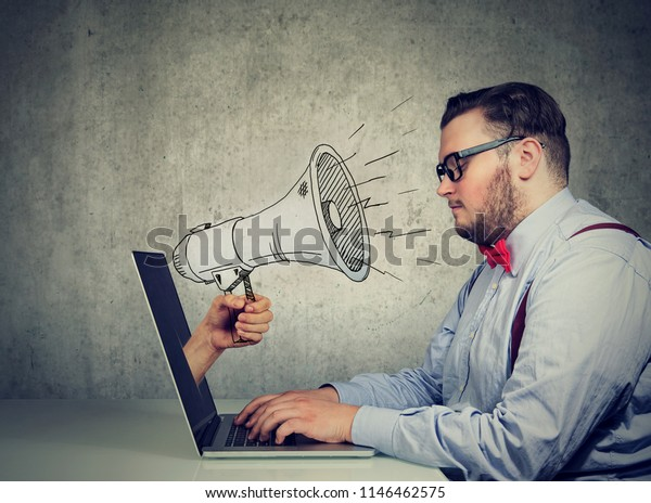 Businessman sitting at table working on computer screaming with a megaphone poking out from a laptop screen