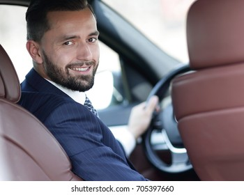 businessman sitting at the wheel of a car and looking at the cam
