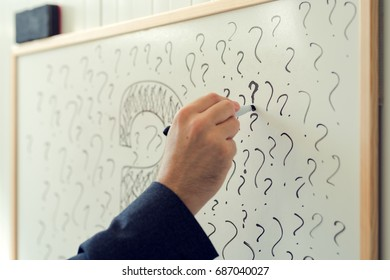 Businessman sketching many question marks on office whiteboard, uncertainty and unpredictability in business