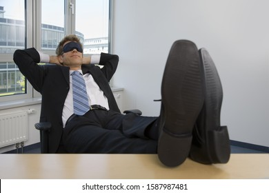 Businessman sleeping with feet up on desk