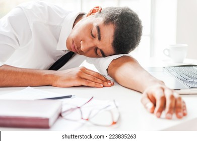 Businessman sleeping. Handsome young Afro-American man in shirt and tie sleeping while sitting at his working place