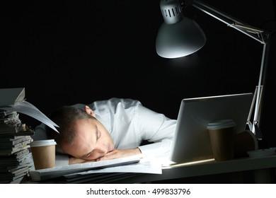 Businessman sleeping at his desk in dark office